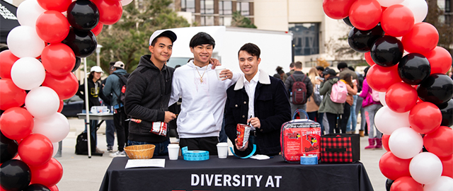 Students at a Diversity Advocacy event under an arch of red, white, and black balloons